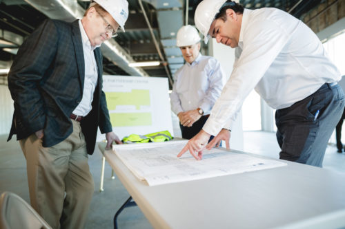 three men in white hard hats looking at blue print on table